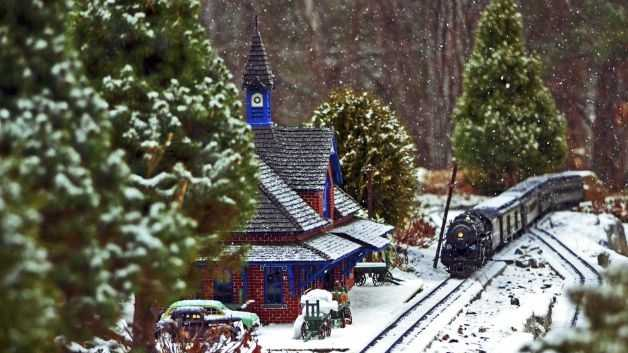 One of Walt Pauli's trains chugs toward the station in the garden train display outside his home in Leominster, Mass.