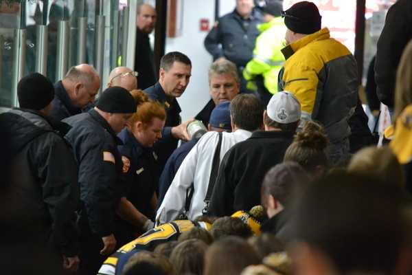 Fans look on as emergency medical technicians tend to a fan who had a seizure during Boston Bruins Practice.  (Matt Schooley, Wilmington.patch.com)