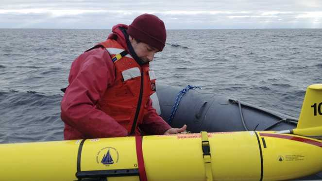 In this Dec. 4, 2012 photo, Woods Hole Oceanographic Institution chief scientist Mark Baumgartner, aboard a ship in the Gulft of Maine, secures an underwater robot, or glider, used to collect acoustic data to help scientists locate endangered whales in the north Atlantic Ocean.