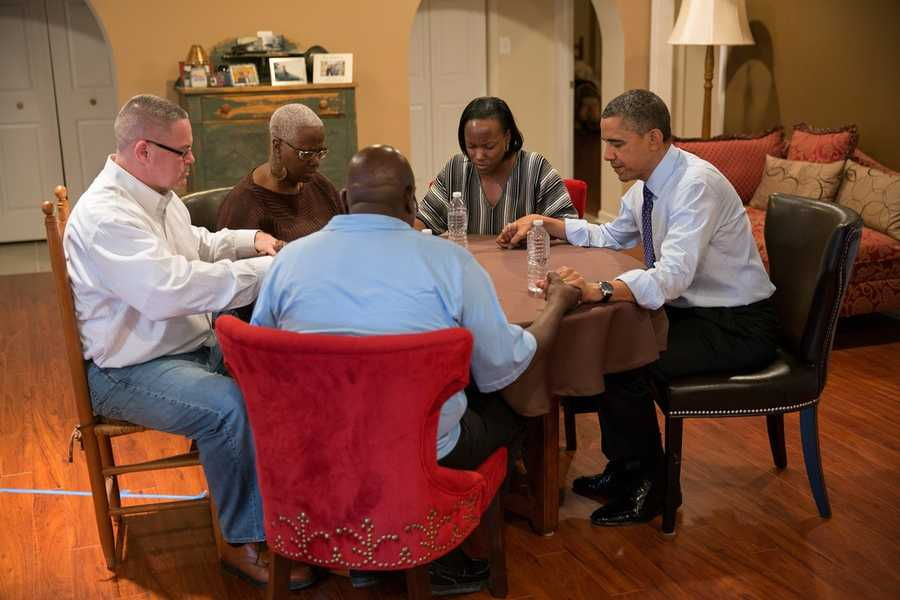 President Barack Obama prays with, from left: Richard Santana, Velma Massenburg, Jimmie Massenburg, and Tiffany Santana, during a visit to the Santana's home in Falls Church, Va., Dec. 6, 2012.