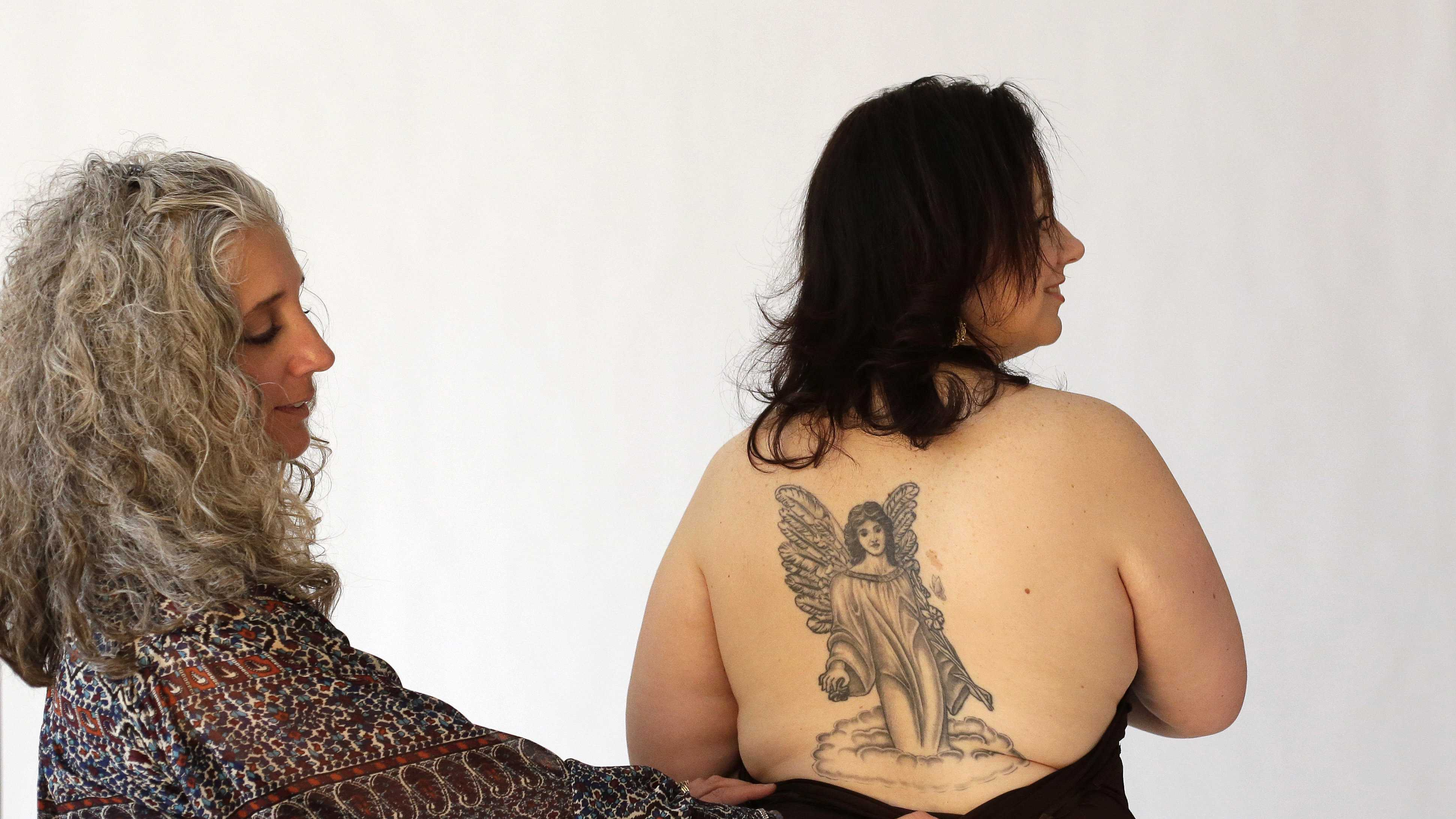 Stephanie Niewola, of Cranston, R.I., right, is directed by Paula McLaughlin, left, during a photo shoot for people with tattoos they had made in honor of those killed or injured during the Station Nightclub fire, in West Warwick, R.I., in February of 2003. Photos from the shoot are to be displayed in an exhibit held to honor those killed or injured in the blaze that took 100 lives.