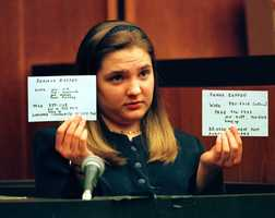 Woodward holds up two index cards showing the phone and pager numbers for the parents of infant Matthew Eappen during her testimony.
