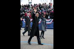 President Barack Obama and First Lady Michelle Obama wave as they walk in the inaugural parade along Pennsylvania Avenue in Washington, D.C., Jan. 21, 2013.