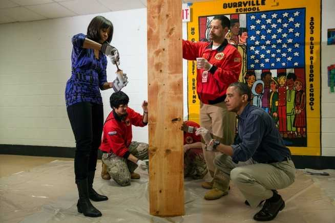 President Barack Obama and First Lady Michelle Obama stain shelves during a National Day of Service school improvement project at Burrville Elementary School in Washington, D.C., Saturday, Jan. 19, 2013.