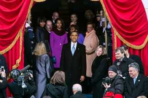 President Barack Obama pauses to look back at the scene before leaving the platform following the inaugural swearing-in ceremony at the U.S. Capitol in Washington, D.C., Jan. 21, 2013. Standing behind the President are First Lady Michelle Obama, daughters Malia and Sasha, and Marian Robinson.