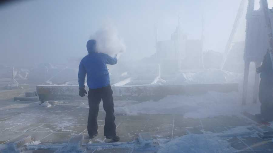 Mike Carmon, Head Meteorologist and Weather Observer throws a pitcher of hot water into the air. Due to the temperature difference, much of this water evaporates, forming a very thick cloud of microscopic water droplets.