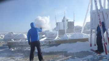 """Mike Carmon, Staff Meteorologist and Weather Observer throws a pitcher of boiling water into the air. Due to the temperature difference, much of this water evaporates, forming a very thick cloud of microscopic water droplets. (""""The Mount Washington Observatory"""" / www.MountWashington.org)"""