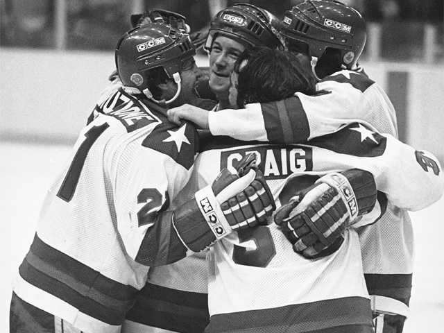 """""""Miracle on Ice""""Michael Eruzione, left, scorer of the decisive fourth goal for the USA in the game against USSR on Feb. 22, 1980 in Lake Placid, is embraced by team mates John O'Callahan, David Silk, and goalie James Craig after he brought his team into the lead. Many on the team attended Boston University."""