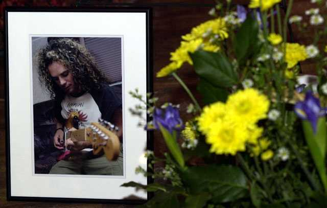 A photo of Great White guitarist Ty Longley rests next to flowers at a tribute to Longley, Sunday, March 2, 2003, at the Yankee Lake Ballroom in Brookfield, Ohio. Longley, 31, was one of the 100 people to die.