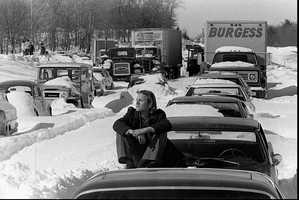 Roy Sodersjerna of Higham, Mass. suns himself on the hood of his car which is stuck in snow on Massachusetts Route 128 in Dedham, Mass. in this Feb. 9, 1978 file photo. Sodersjerna, who waits for plows and tow trucks to dig him out, has been living at a Red Cross shelter nearby since being trapped in the storm three days earlier.