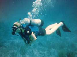 """""""In the summer, boating and searching for sea glass,"""" she says, pictured here scuba diving."""