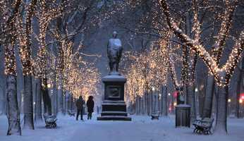 A couple walks down the illuminated, snow-covered Commonwealth Avenue Mall in Boston