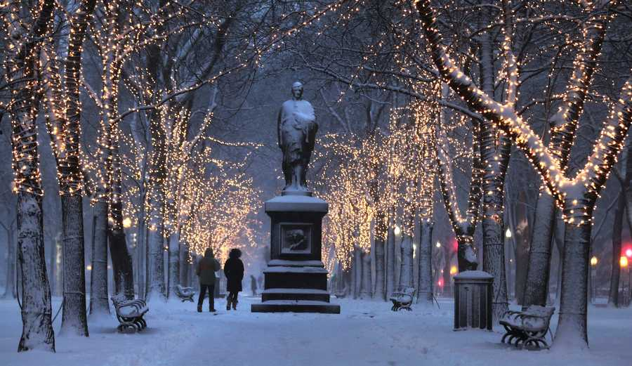 A couple walks down the illuminated, snow-covered Commonwealth Avenue Mall in Boston