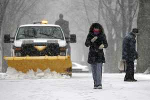 A snow plow clears the path in the park along Commonwealth Ave in Boston.