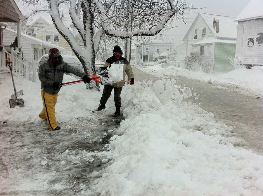 Building a snow dam to keep the water out on flooded Babcock Street in the Houghs' Neck section of Quincy.