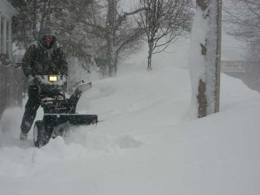 A Charles Street resident works to clear the sidewalk Saturday morning in Malden
