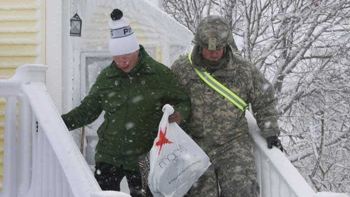 Sgt. Thomas Jones, 35, of Plymouth, a squad leader with the 10-58th Transportation Company out of Hingham, helps a Hull resident out of her home who lost power during the February blizzard.