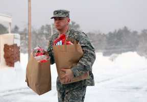 A National Guardsman brings supplies to the Furnace Brook Middle School on Saturday afternoon as people from Duxbury, Scituate and Marshfield start to arrive there to escape the cold.