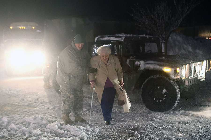 An evacuee is helped into the Furnace Brook Middle School on Saturday evening by a National Guardsman in Marshfield.