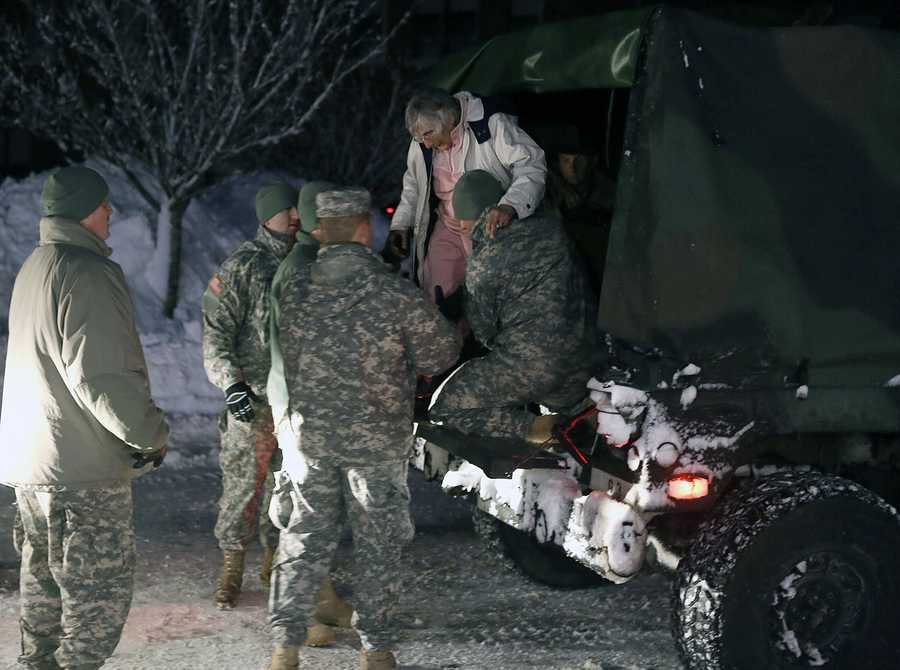 An evacuee is helped from the back of a National Guard truck in Marshfield in February 2013.