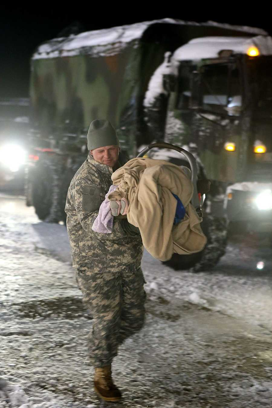 A National Guardsman brings a young baby into the Furnace Brook Middle School  in Marshfield.