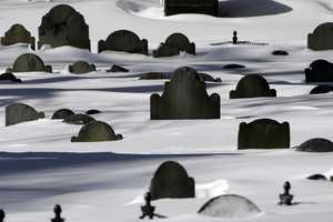 Grave markers in the Granary Burial Ground, that date back to 1660, are partially buried in snow on a sunny Sunday afternoon, Feb. 10, 2013 in Boston.