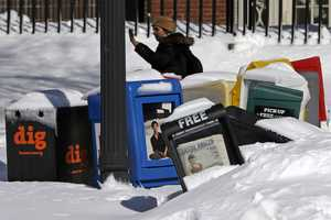 A row of paper boxes are partially buried in snow in Boston Common, Sunday, Feb. 10, 2013 in Boston.