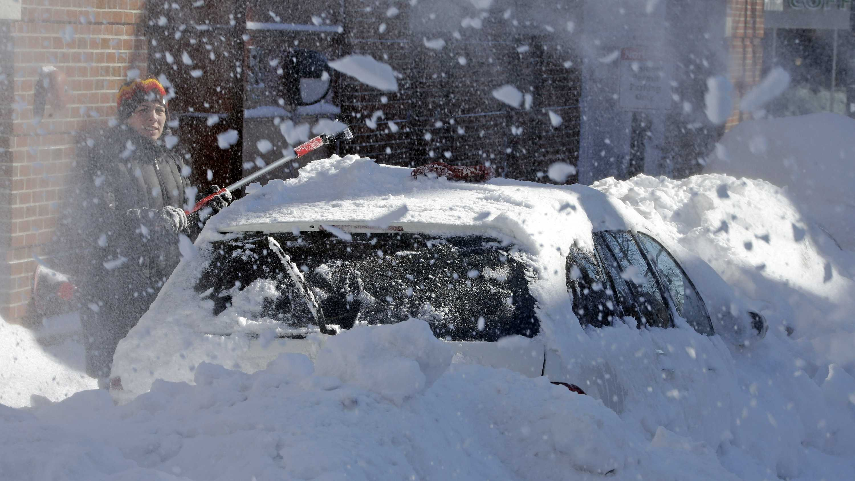 A woman on North street in the North End neighborhood of Boston, digs out her car as a neighbor runs a snow blower, Sunday, Feb. 10, 2013.