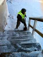 Sgt. Steven Gilmore, of the 772nd Military Police Company, 211th Military Police Battalion, shovels snow off of the stairs of a home in Marshfield