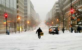 A pedestrian makes his way up snow-covered 20th Street NW at K Street NW in the heart of the Washington business district.