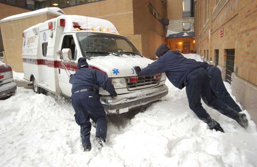 Myren Green, left, an Emergency Medical Technician, David Hayburn, center, a nurse, and Robert Bethea, right, an Emergency Medical Technician, push an ambulance out of the snow, Feb. 17, 2003, at Jefferson Hospital in Philadelphia.
