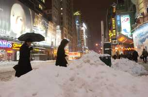 Pedestrians make their way between snowdrifts as they cross 42nd Street in New York's Times Square, Feb. 17, 2003.