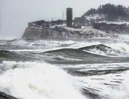 During the noontime high tide, heavy seas crash against the Humarock section of Scituate, Mass., Feb. 18, 2003, the day after a severe winter storm dumped about two feet of snow in the Boston area.