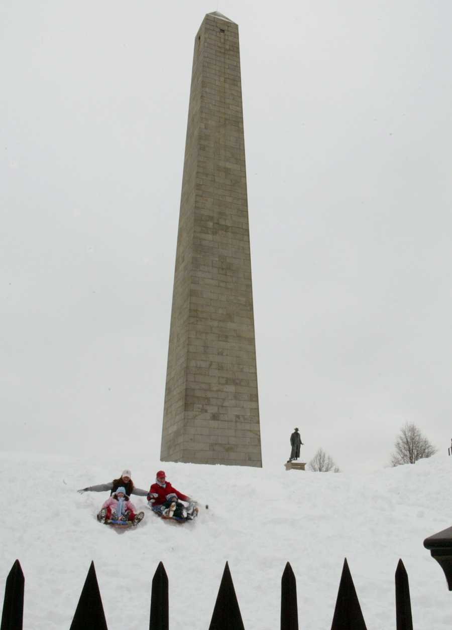 Melinda Pierce and her 5-year-old daughter Macie, left, Kelly Moloney and her 4 year-old son Devin, right, enjoy the slide at Bunker Hill National Historical Park in Boston.