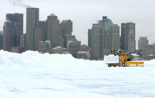 Snow is cleared from the south cargo area of Logan Airport with Boston as a backdrop following a blizzard Tuesday, Feb. 18, 2003 in Boston.