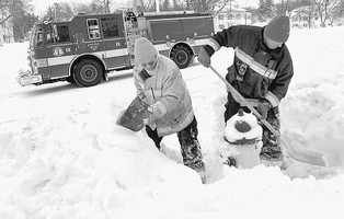 A firefighter digging out a hydrant with some help on the South Shore