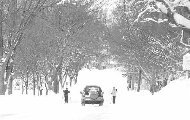 Cross-country skiers share the road with a car on the South Shore