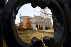The Elms mansion as seen through an opening in an iron fence, in Newport, R.I.