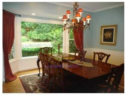 A formal dining room with a bay window.