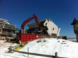 Crews begin the process of tearing down condemned homes on Plum Island Saturday morning.