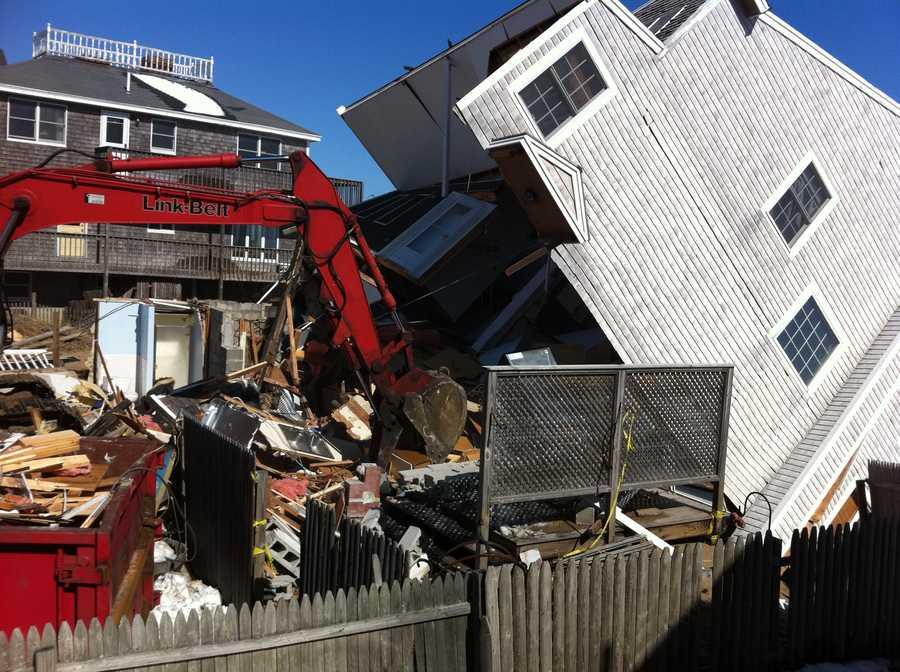 Heavy equipment operators tear down remnants of Plum Island homes.