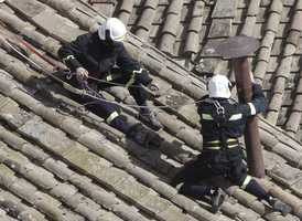 Firefighters place the chimney on the roof of the Sistine Chapel, where cardinals will gather to elect the new pope, at the Vatican, Saturday, March 9, 2013.