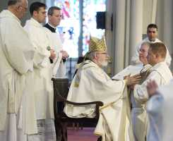May 26, 2007: O'Malley clasps the hands with Father Daniel Kennedy, right, during an ordination Mass at the Cathedral of the Holy Cross.