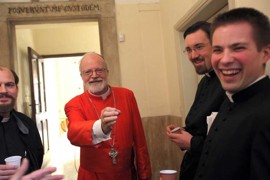 Cardinal Sean O'Malley jokes with fellow priests before celebrating Mass at his titular church in Rome, Santa Maria della Vittoria, on March 10, 2013.