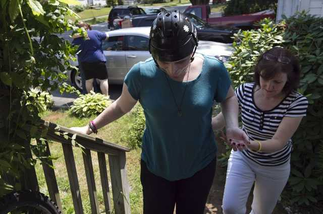 In this Thursday, Aug. 2, 2012 photo, Meg Theriault is assisted by her mother, Deb Theriault, right, as she arrives at their home in Salisbury, Mass., for the first time since she was involved in the multi-fatal minivan crash.