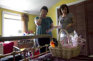 In this Thursday, Aug. 2, 2012 photo, Meg Theriault, left, is helped by her mother, Deb Theriault, as Meg examines her personal belongings after not being in her bedroom for eight months.