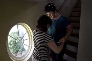 In this Thursday, Aug. 2, 2012 photo, Meg Theriault is assisted by her mother, Deb Theriault, left, as they descend a flight of stairs at their home in Salisbury, Mass.