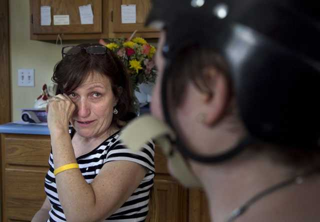 In this Thursday, Aug. 2, 2012 photo, Deb Theriault, left, wipes a tear from her eye from joy that her daughter survived the crash.