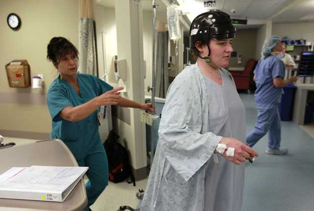 In this Tuesday, Sept. 4, 2012 photo Meg is escorted by nurse Darleen Crisileo, left, during preparations for surgery at Massachusetts General Hospital, in Boston. Theriault had a plastic plate about five inches long installed during the surgery where a portion of her skull had been removed following the near-fatal head injury sustained during the crash.