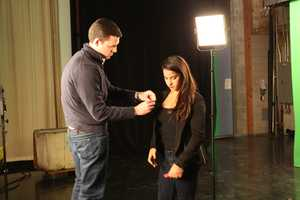 Photographer Richard Feindel helps Raisman with a microphone in preparation for a promotional shoot following the interview.